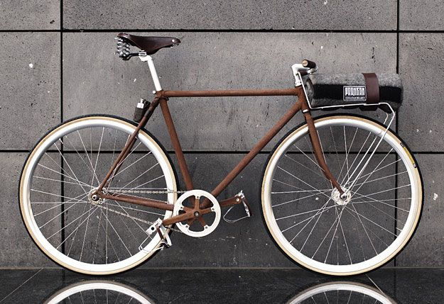 Behold, 'FeO2′, a steel frame that has been forcibly oxidized and accessorized with a selection of contrasting textures. A front rack has been installed that houses an army surplus woolen blanket, secured by a regulation leather belt. The custom leather pouch mounted behind the seat tube houses a hip flask in the form of a jerry can which continues the military theme.
