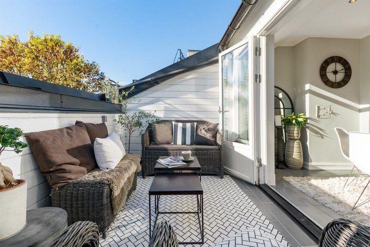 Terrasse tropézienne aménagée avec un salon de jardin en résine tressée et décorée dun