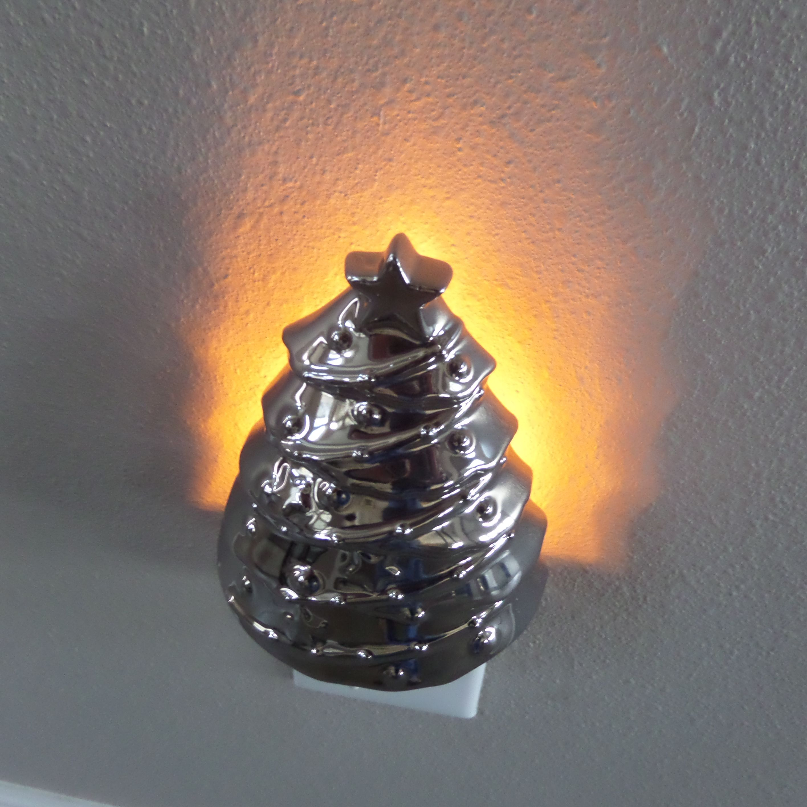 Silver tree Christmas. Silver plug in tree. It shines a tree on the wall. I don't recall where I ...