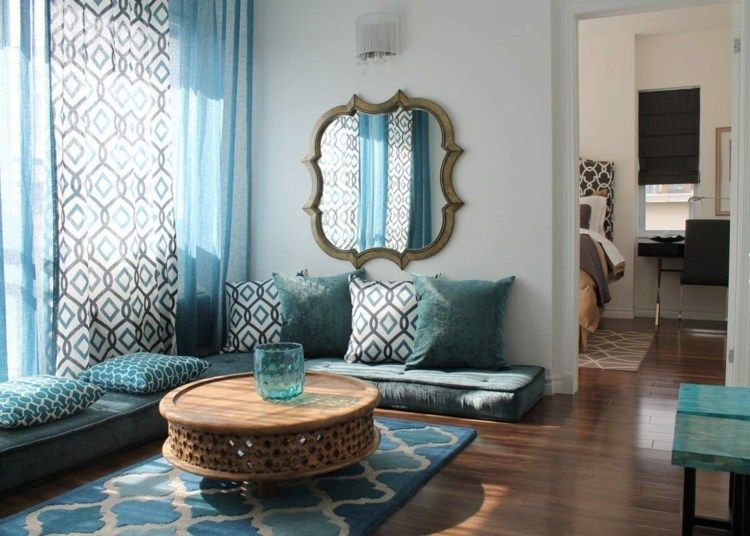 Ein Sofatisch im Ethno Stil vor den blaugrünen Bodenkissen - wohnzimmer ideen orientalisch