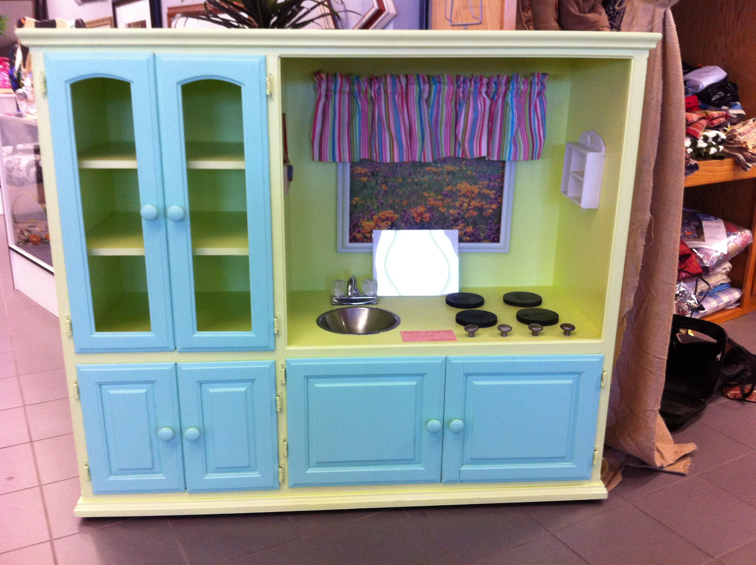 Play kitchen made out of old entertainment center. Saw this at a ...