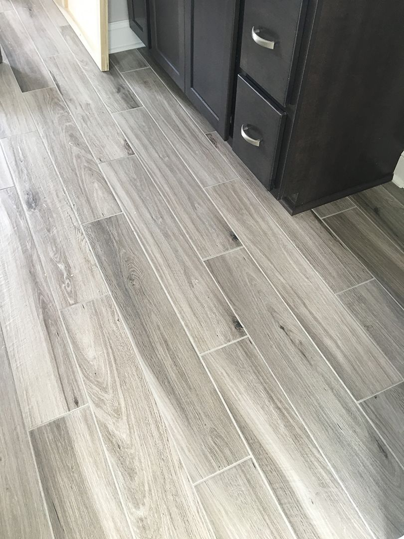 Newly installed gray weathered wood plank tile flooring for Hardwood floors in bathroom