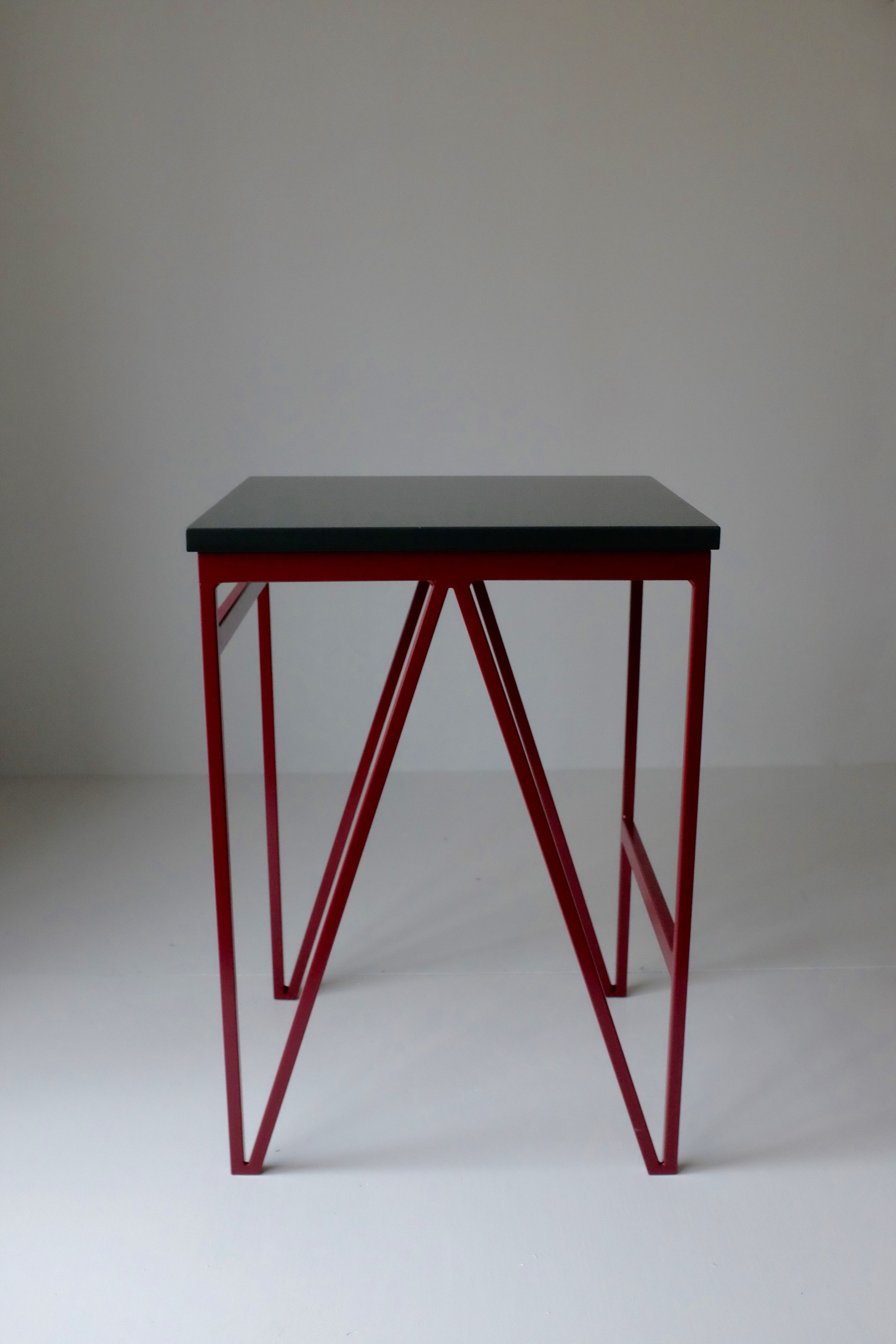 Beetroot powder coated steel frame and deep green colour lacquered plywood top minimal modernbritishfurniture powdercoatedsteel stool