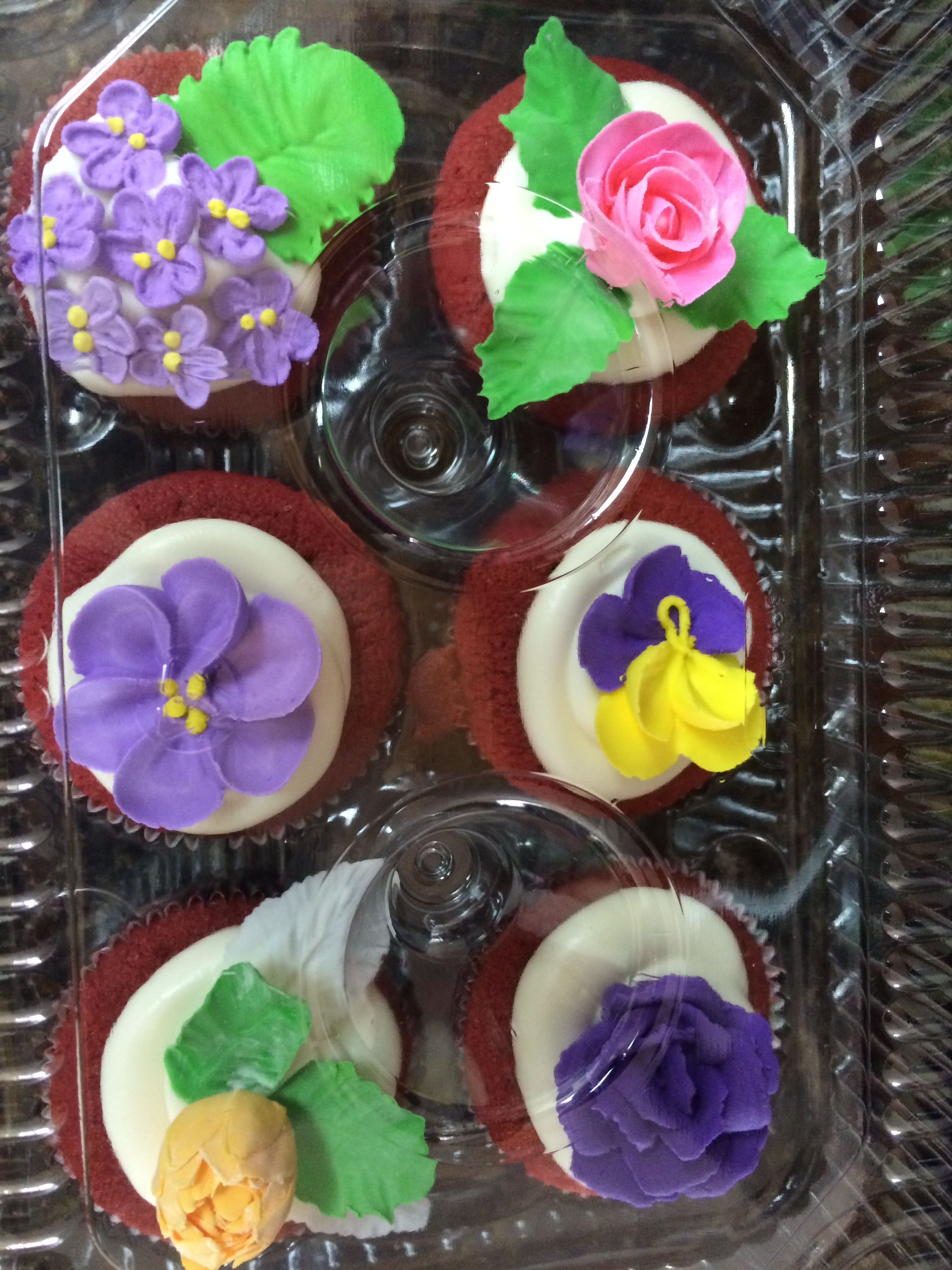 Red velvet cupcakes with him paste or royal icing flowers.