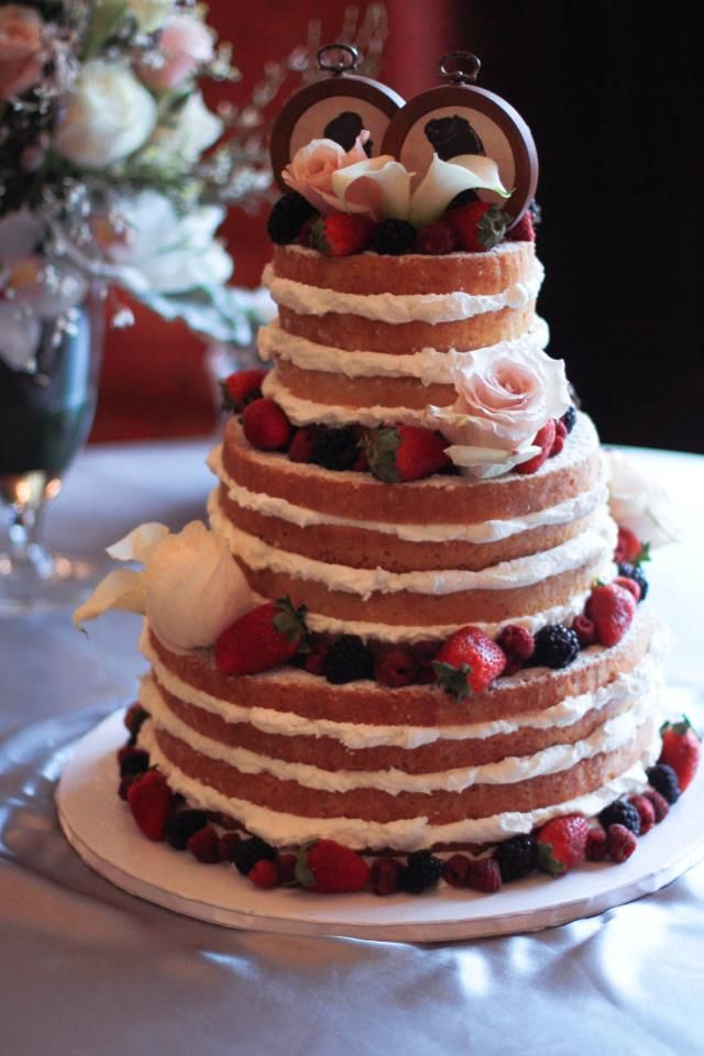 """A """"naked"""" wedding cake that fit this bride's garden theme so perfectly!  Garnished with fresh fruit, real flowers, and vintage cake topper silhouettes from the bride."""