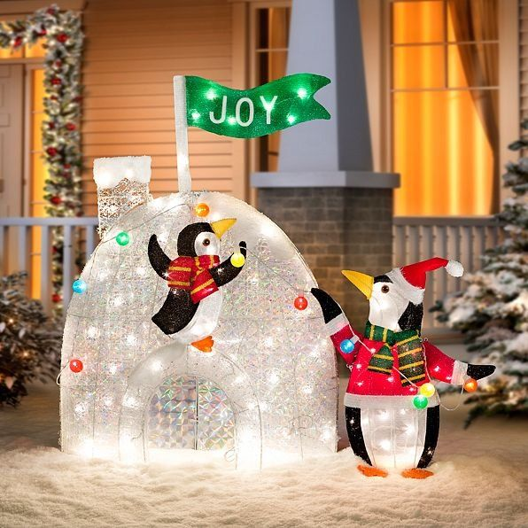 these penguins decorating igloo outdoor christmas decoration are getting ready for the season the joyful flag atop the icy igloo looks as if its blowing