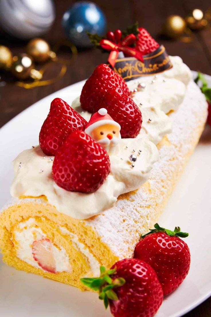 Mouthwatering Japanese Christmas Cake with a tender buttery spongecake rolled with sweet juicy strawberries and whipped cream. #christmasrecipes #japanesefood #rollcake #christmasdesserts