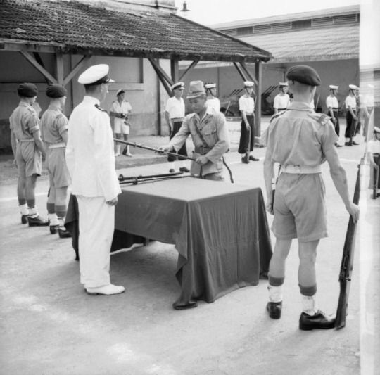 A Japanese naval officer surrenders his sword to a British Lieutenant in Saigon on 13th September, 1945