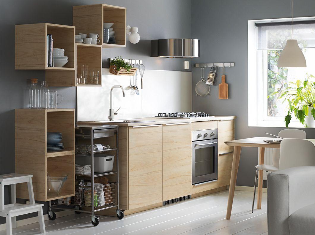 Cucina con elementi a giorno e mobili con ante in legno chiaro