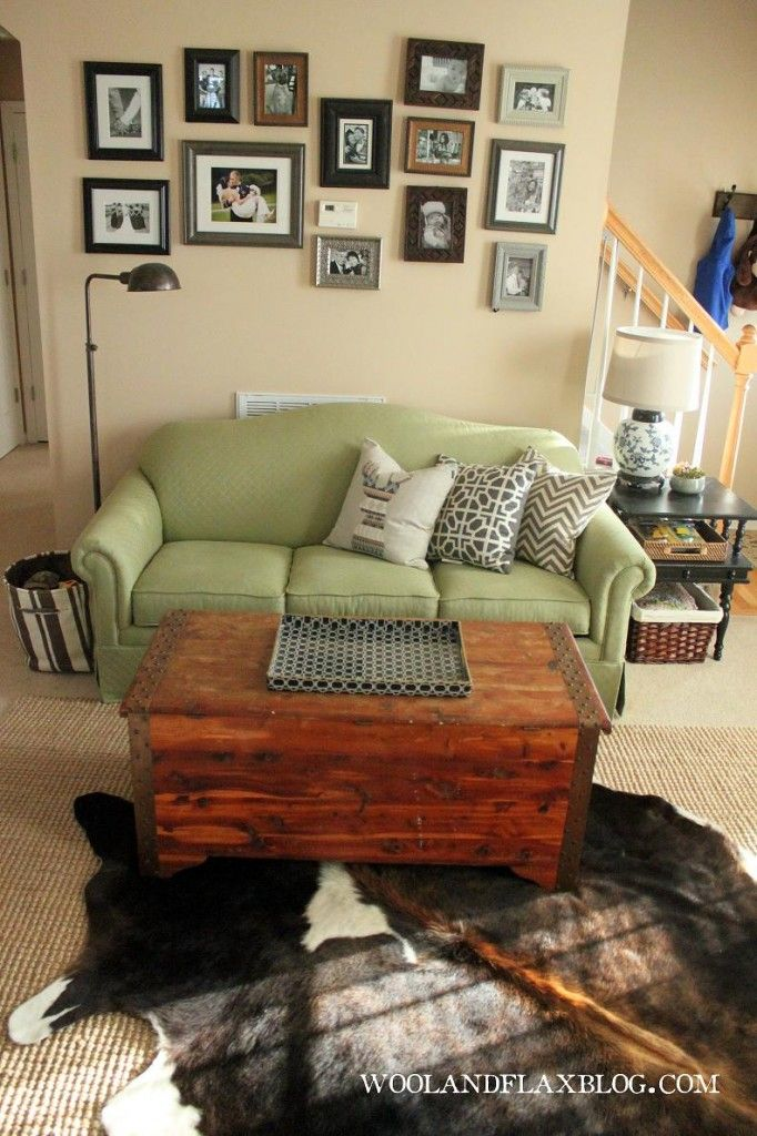 eclectic living room; green couch; cowhide rug