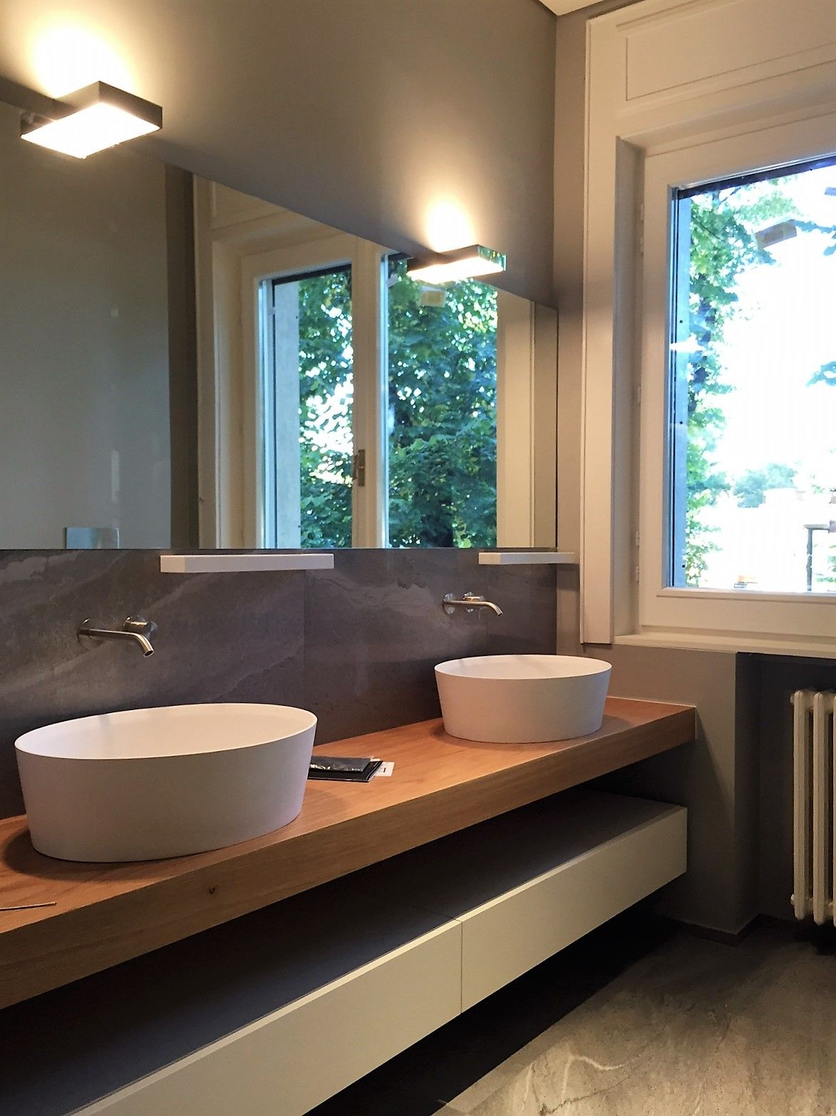 bagno con piano in legno e doppio lavabo in corian
