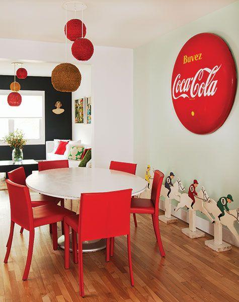 salle a manger avec table blanche chaises rouges luminaires suspendus de couleur et affiche coca cola