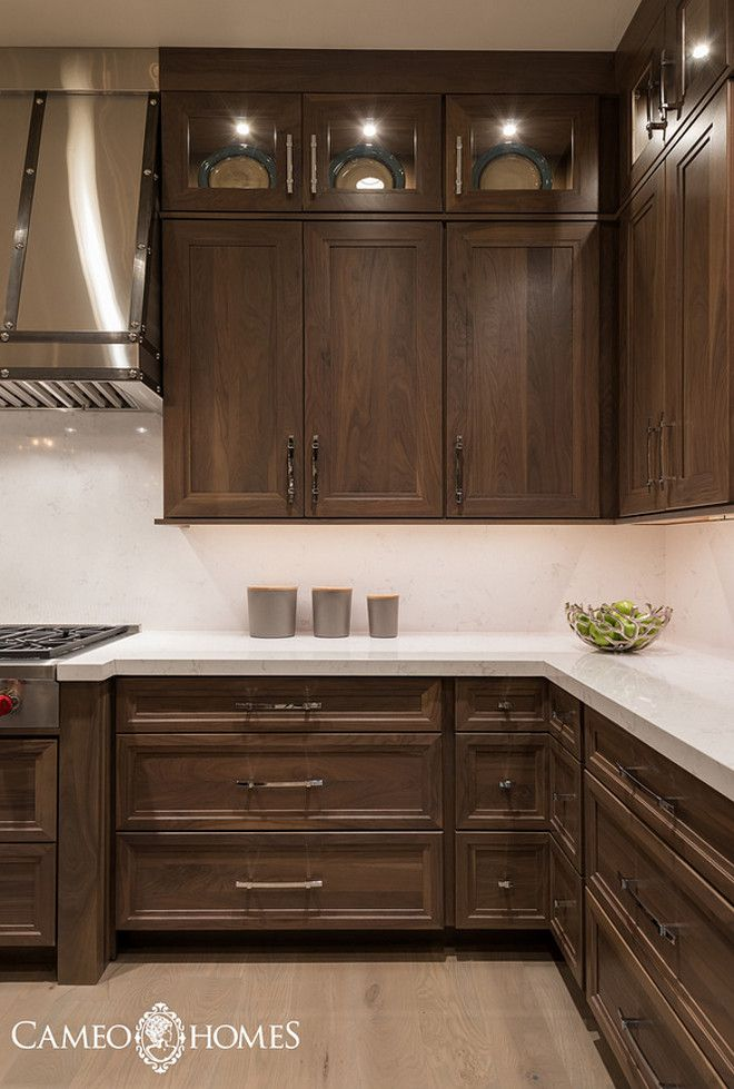 Elegant walnut cabinets with bright and streamlined hardware propels the traditional into  contemporary era via homebunch also brown kitchen cabinet designs for warm natural look rh pinterest