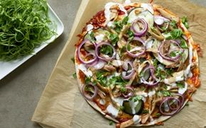 Krydret pizza med hvidløgsdressing og salat En fyldig pizza med med frisk salat og dressing - velbekomme.