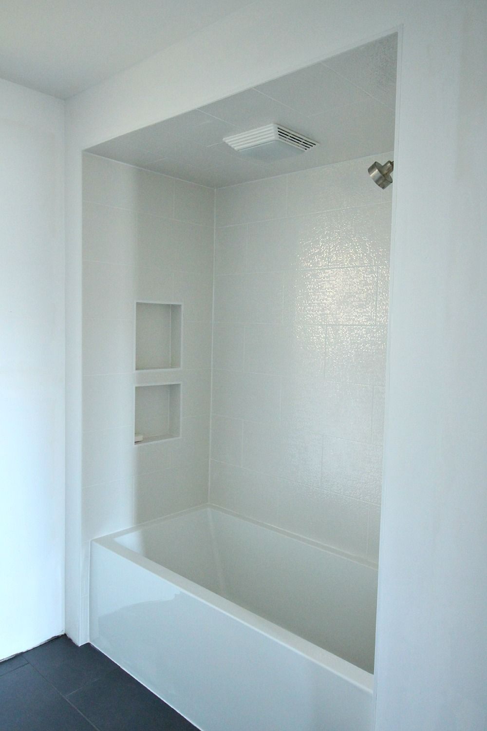 sparkly white tub surround tile with charcoal grey tile floor