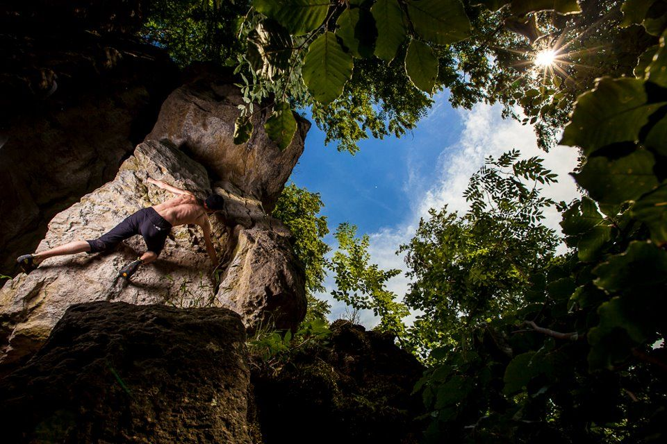 Davide Fracasso venturing up the exposed boulder deep in the forests of Hertz  Photo : Alpine-Photography by Kamil Tamiola