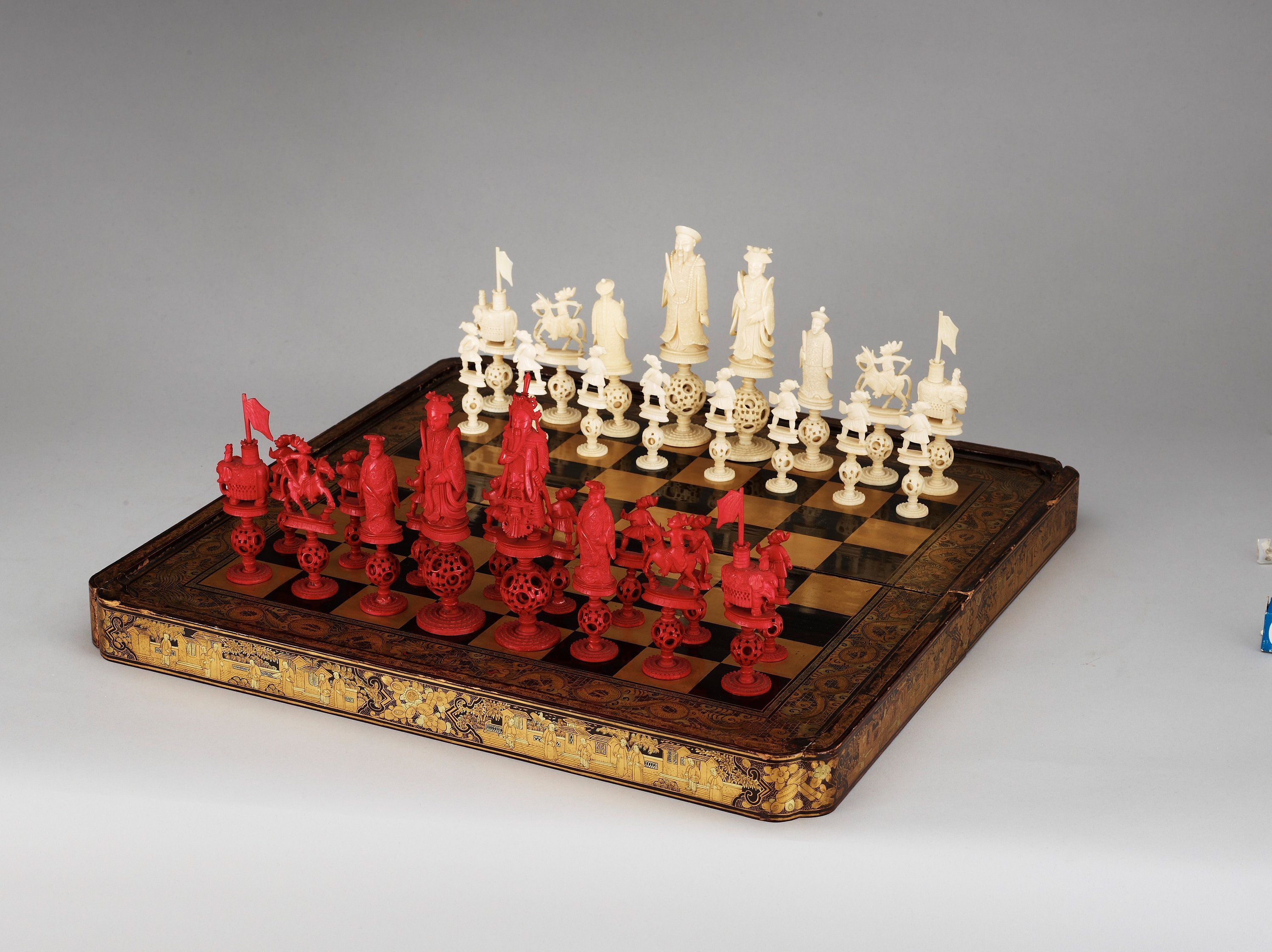 An large lacquered Games Box with ivory and bone Chess Pieces, Qing dynasty. With a hinged lid opening to reveal a bakgammon board, the chequered exterior forming a chess board with alternate squares of gold and black. Comprising 32 pieces carved as members of the chinese court.