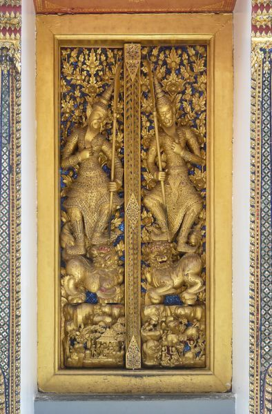 Metal door with intricate Asian design coated in gold ...