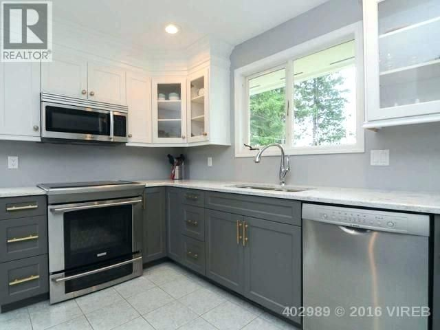a kitchen with white top cabinets and dark bottom cabinets ...