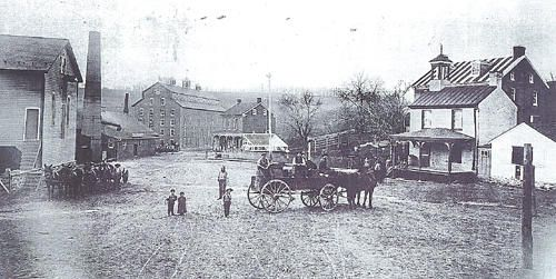 A photo from 1900 shows Glen Rock with the Foust Distillery smokestack in the background. After being struck by lightning two weeks ago, the only remaining piece of the building will be torn down. (Glen Rock Historical Preservation Society photo)