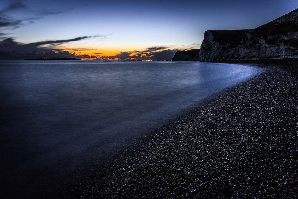 A picture of the sunset fading over Weymouth and Portland captured from the beach right next to Durdle Door