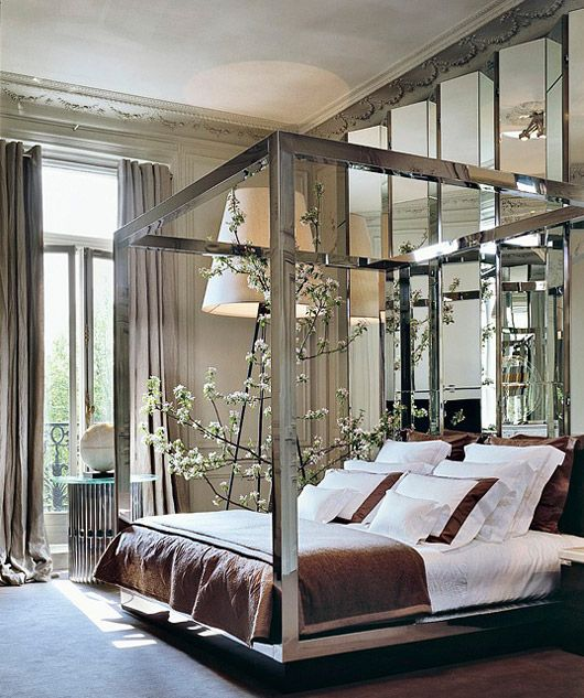 ... prominent pieces like an oversized floor lamp and a wall of mirrored  room divider, a sleek and gorgeous modern chrome finished four poster bed  still ...