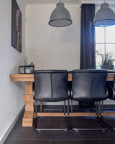 stoere eethoek met zwarte stoelen en kloostertafel. Mooie betonlook ...