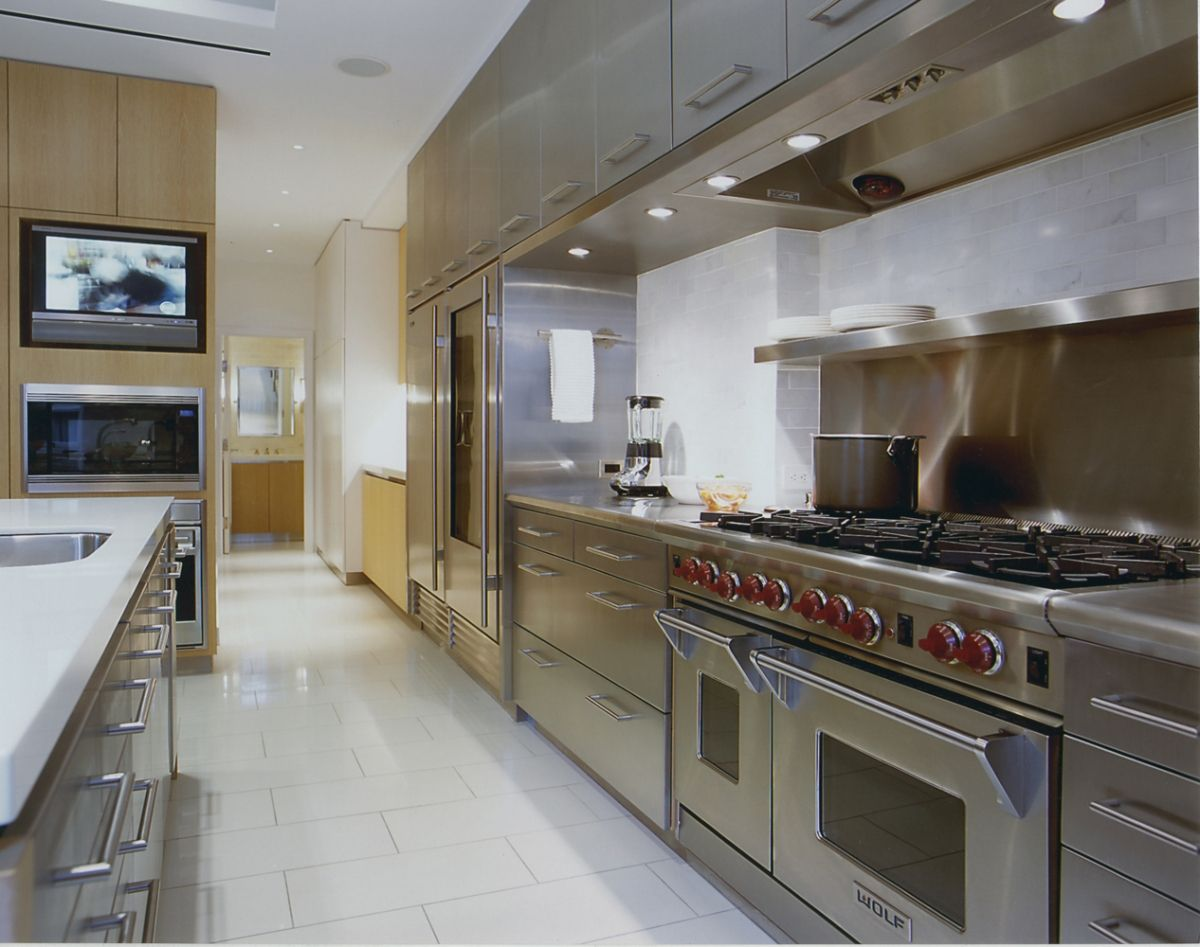 Professional looking stainless steel kitchen; built-in TV of same proportions as built-in microwave; marble subway tile; Wolf oven and range; Michael Neuman Architecture