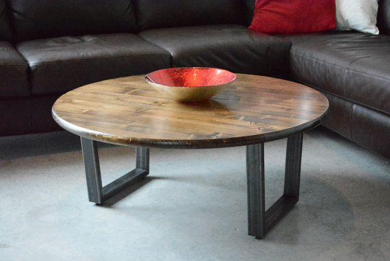 Round coffee table made with a knotty pine top and a steel base The