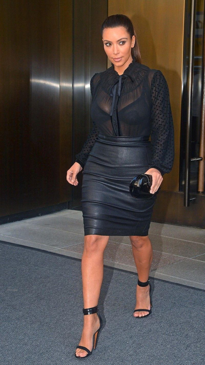 Kim Kardashian wearing a black sheer blouse and leather pencil ...