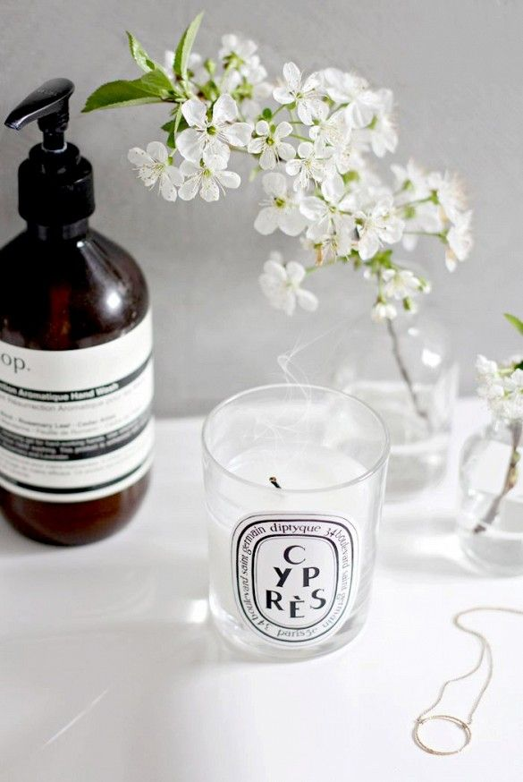 Diptique candle and Aesop soap at sink.