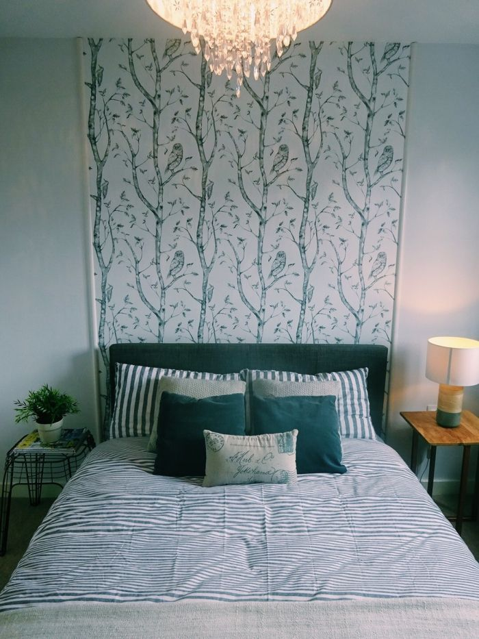 a wallpaper with a natural pattern that enhances the peacock blue headboard, i …