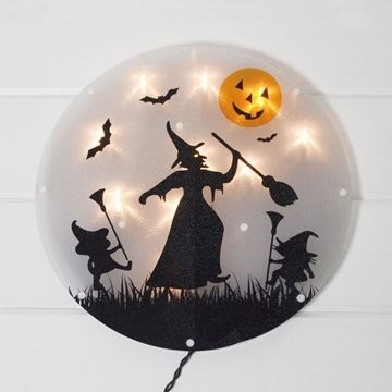 Greet trick-or-treaters with the glow of this window decoration featuring a witch silhouette and jack-o-lantern moon!