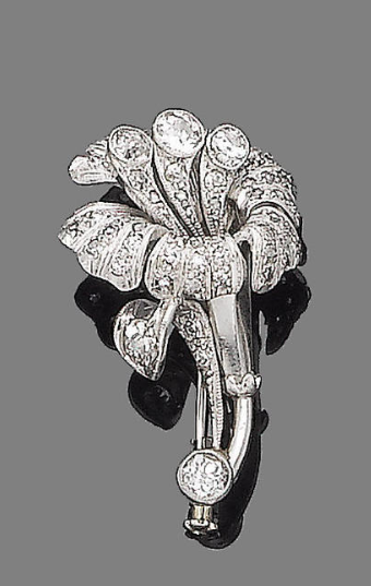 A diamond flower brooch  Modelled as a lily, the petals millegrain-set with single and rose-cut diamonds, the pistils, leaves and stem with collet-set old brilliant-cut diamonds, diamonds approx. 0.85ct total, length 2.9cm