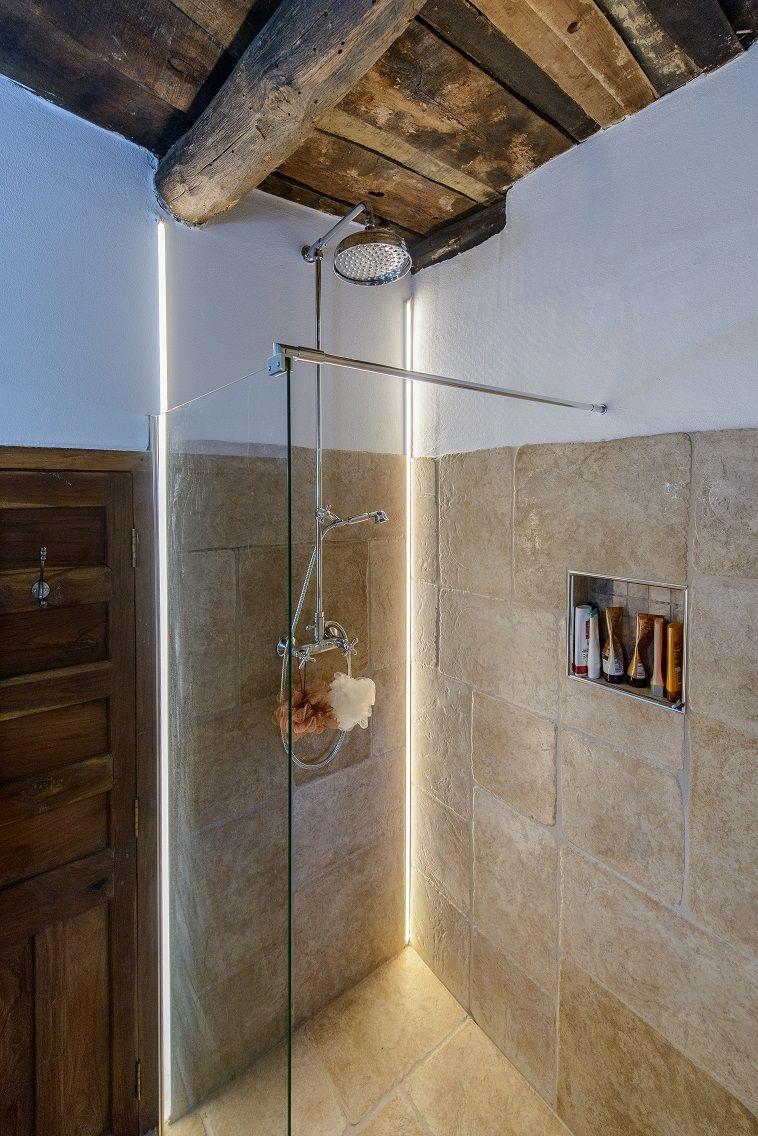 Elegante doccia a filo pavimento illuminata da un profilo