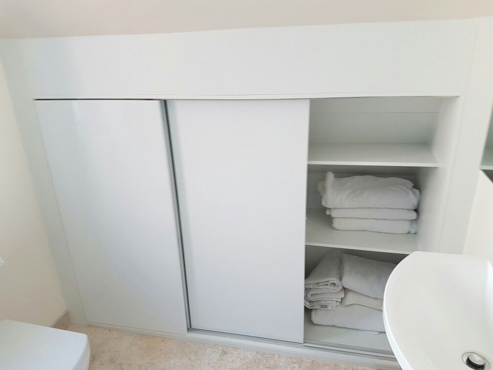 Bespoke Bathroom Storage Built Into Eaves Of Roof With Sliding