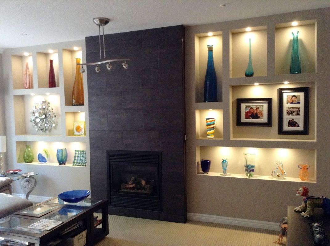 Fireplace feature wall with wall niches and dark tiled fireplace