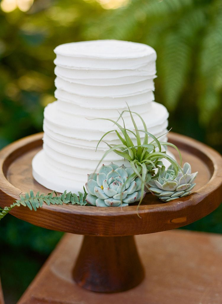 Simple, two tier white wedding cake on a wooden stand