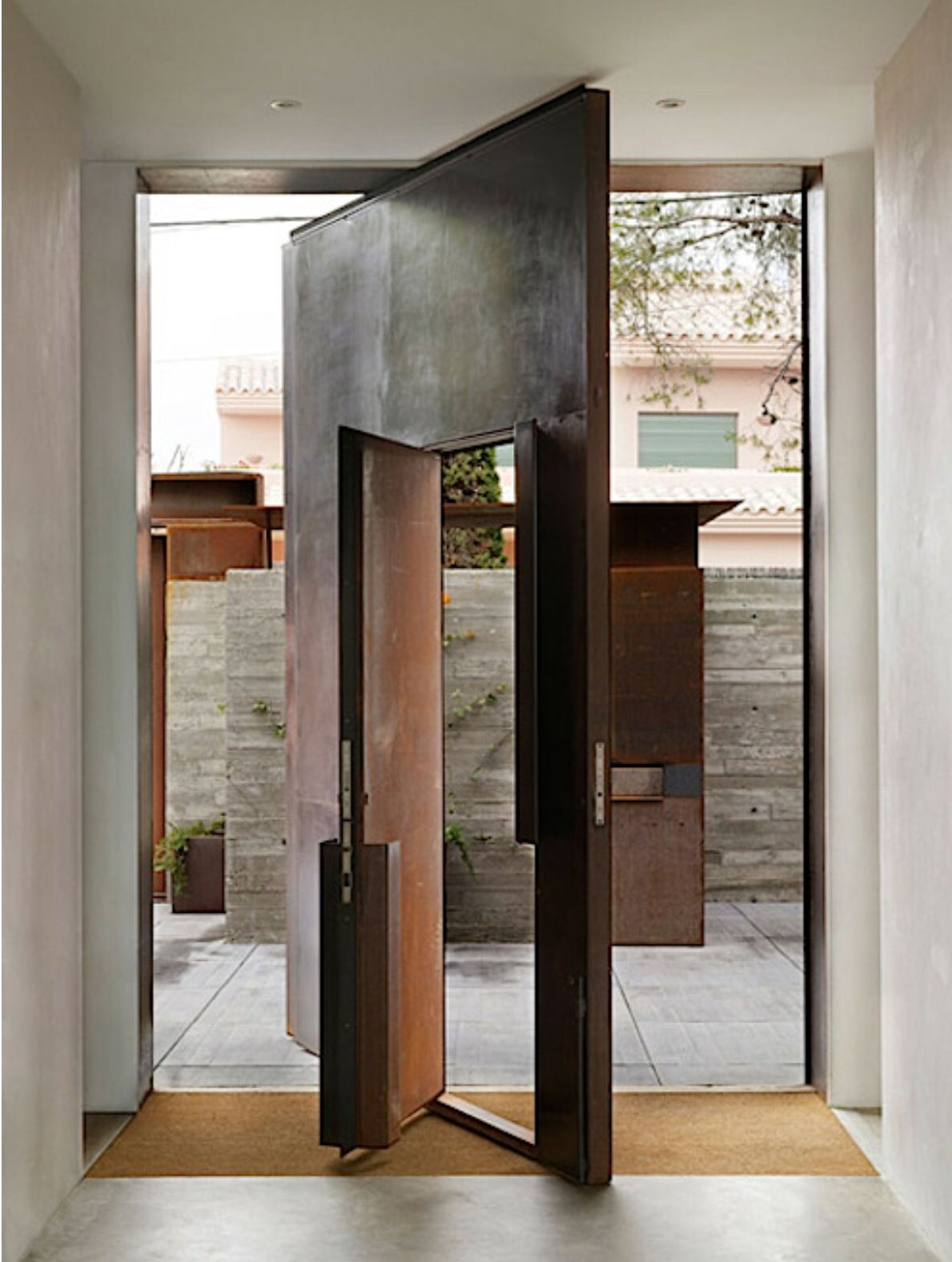 Corten steel pivoted front door with inset swing door for Big entrance door