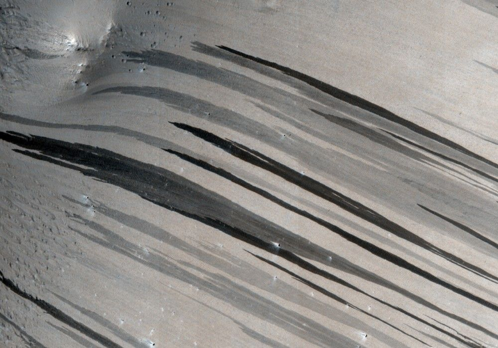 Multiple Generations of Dark Slope Streaks on a Crater in Arabia Terra This image is of a crater in Arabia Terra, which is a large swath of bright (high albedo) terrain in the Martian cratered uplands. The steep interior walls of the crater are covered with numerous slope streaks, thought to be caused by dust avalanches that strip away layers of dust to reveal a darker underlying surface.
