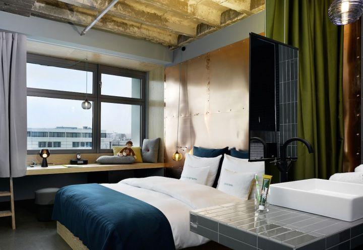 """Gli interni delle stanze del 25Hours Hotel Bikini Berlin a tema """"Urban"""", con un design più freddo e colori che richiamano il concetto di grande città"""