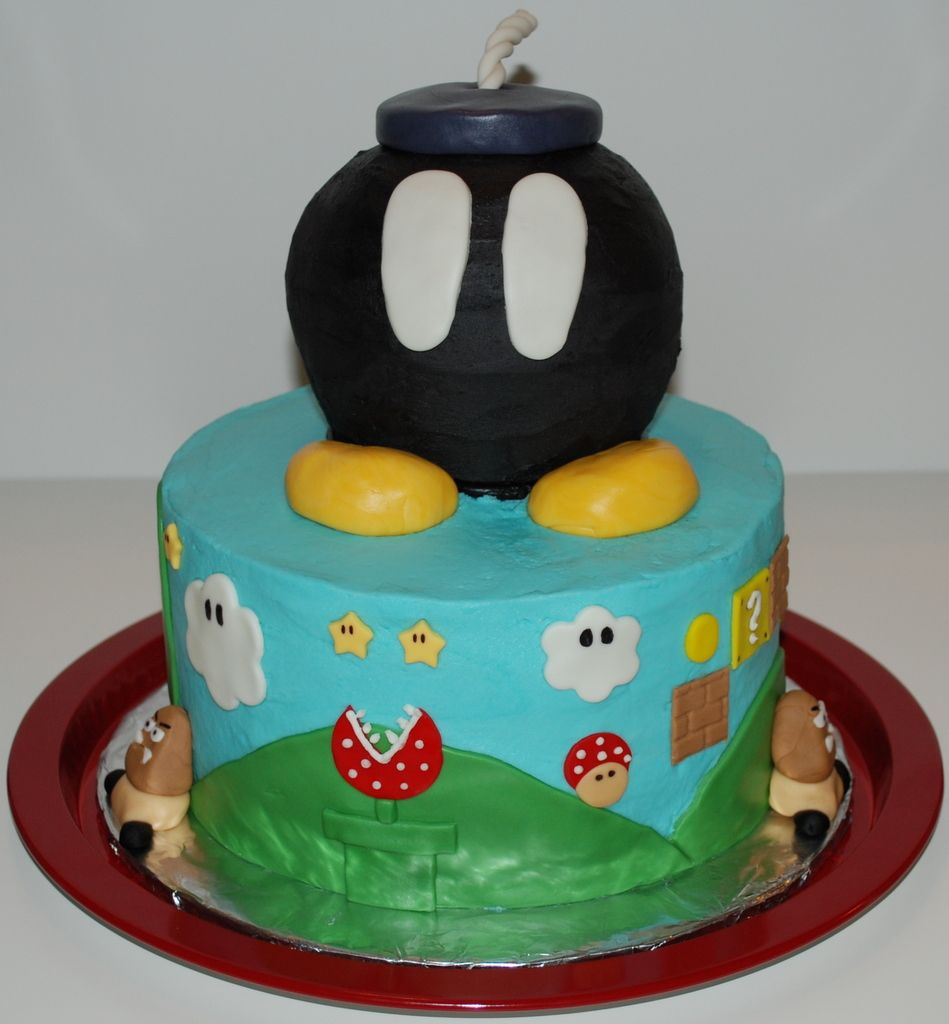 "Super Mario Bomb Cake - My son saw a cake like this on Flickr and asked if I could make it for his birthday.  What good is it having a mom that makes cakes if you can't get the cake you want?  So I turned in and this is the cake he ended up with. The bottom is made of two layers of chocolate cake and one layer of vanilla cake. The ""bomb"" on top is half chocolate cake and half vanilla cake. The cake is frosted in vanilla buttercream on the bottom tier and chocolate buttercream on the ""bomb""…"
