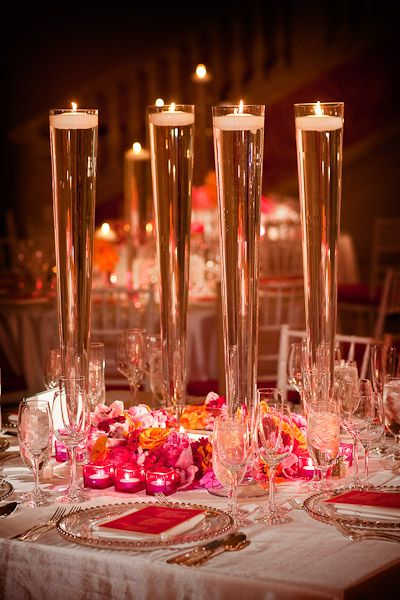 Tall footed vases with water and floating candles