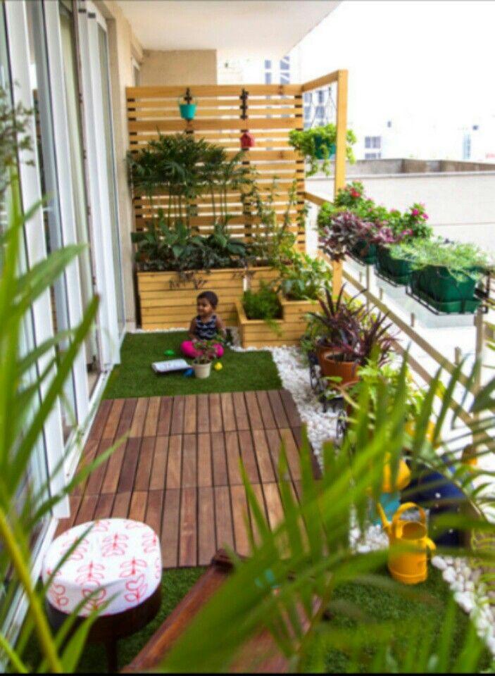 Aménager un balcon étroit avec brise vue en bois pin et sol en bois teck moquette en fausse pelouse cailloux et multitude de plantes