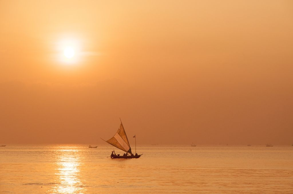 Golden sunrise at Kenjeran Beach, Surabaya, Indonesia with the fisherman boat.