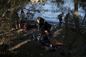 A Syrian refugee woman holds a child as refugees and migrants arrive on Lesbos by boat