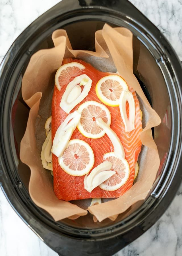 I thought my mother had taught me all of her best tricks in the kitchen, but no — she had one more for me, which she casually let drop while in the middle of our Costco shopping expedition. It's this: She buys bulk salmon from Costco and cooks it all at once in the slow cooker. And it's darn good. Not only is the slow cooker fantastic for this kind of batch cooking, it's also an extremely good way to ensure tender, succulent salmon every time, no matter how many fillets you're cooking…