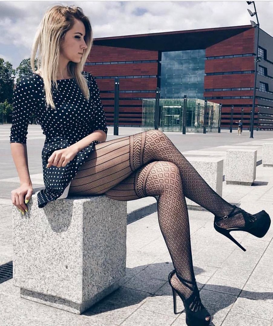 Pretty legs in sexy fishnet stockings and stiletto high heels stock photo