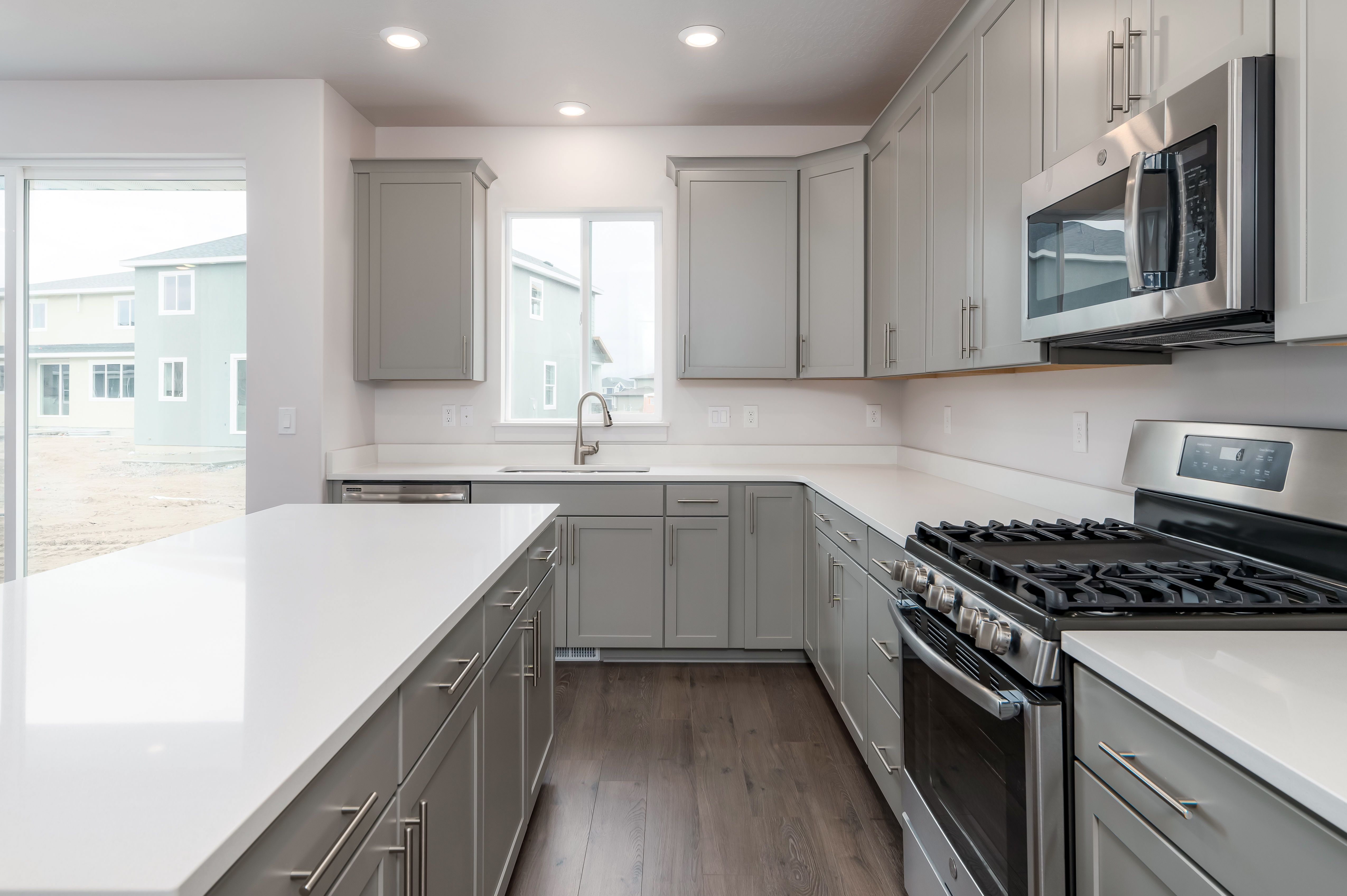 White Quartz Countertops And On Trend Gray Cabinetry Give This