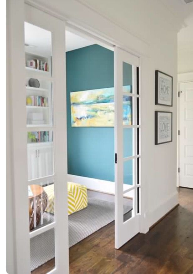 Make a pocket door like this and put photographs over glass panes ...